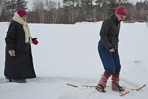 Women snowshoeing through thick snow.